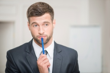 Close-up portrait of handsome businessman in office interior touching his lips with a pen and looking aside and thinking, making some decision with copy place